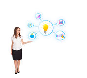 Young woman presenting light bulb with colorful graphs and diagr. Ams isolated on white Royalty Free Stock Photo