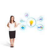 Young woman presenting light bulb with colorful graphs and diagr. Ams isolated on white Stock Photo
