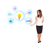 Young woman presenting light bulb with colorful graphs and diagr Royalty Free Stock Photos