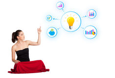 Young woman presenting light bulb with colorful graphs and diagr. Ams isolated on white Stock Photography