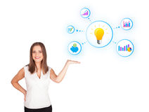 Young woman presenting light bulb with colorful graphs and diagr Stock Image
