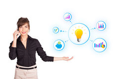 Young woman presenting light bulb with colorful graphs and diagr. Ams isolated on white Stock Photos