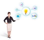 Young woman presenting light bulb with colorful graphs and diagr Stock Photo