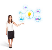Young woman presenting light bulb with colorful graphs and diagr. Ams isolated on white Royalty Free Stock Images