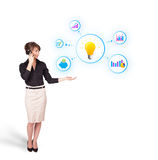 Young woman presenting light bulb with colorful graphs and diagr. Ams isolated on white Stock Image