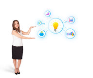 Young woman presenting light bulb with colorful graphs and diagr. Ams isolated on white Royalty Free Stock Photography