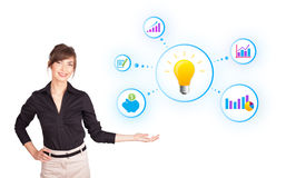 Young woman presenting light bulb with colorful graphs and diagr. Ams isolated on white Royalty Free Stock Photos