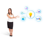 Young woman presenting light bulb with colorful graphs and diagr. Ams  on white Stock Photo