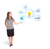 Young woman presenting light bulb with colorful graphs and diagr. Ams  on white Stock Photos