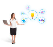 Young woman presenting light bulb. With colorful graphs and diagrams isolated on white Stock Photo
