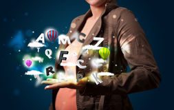 Young woman presenting magical abstract clouds and balloons conc Stock Image