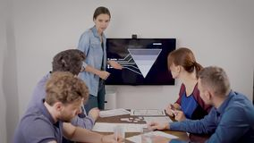 Young woman is presenting report for her colleagues at business meeting in office room, showing data on display