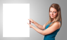 Young woman presenting white paper copy space Stock Photos