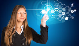 Young woman pressing button within pointer finger. Touching button social network future interface. Businesswoman pressing light point within pointer finger on Stock Images
