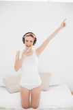 Young woman pretending to sing while listening to music with closed eyes Royalty Free Stock Photography