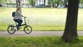 Young woman pretty blonde riding fast on a folding bicycle in a city park stock footage