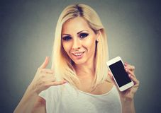 Young woman pretty smiling holding phone showing call me sign hand gesture looking at you camera Stock Photos