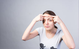 Young Woman Pricking Pimple on Forehead Seriously Stock Image