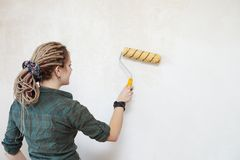 Young woman primed the wall. Young woman primed the wall Stock Photography
