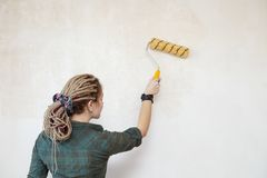 Young woman primed the wall. Young woman primed the wall Royalty Free Stock Photos