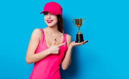 Young woman with prize cup. Beautiful young woman in swimsuit with prize cup standing on the wonderful blue background Royalty Free Stock Image