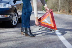 Young woman problem with the car on the road. Car on the roadside a woman holding a warning triangle Stock Photography