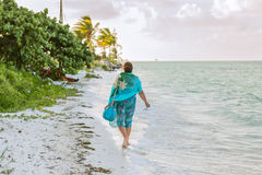 Young woman walking on the beach along the ocean Royalty Free Stock Photography