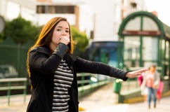 Young woman with protective mask overing her mouth with one hand and asking for a taxi with her other hand on the street Stock Photos