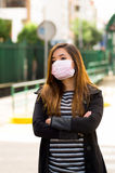 Young woman with protective mask on the street in the city with air pollution with her arms crossed, city background Royalty Free Stock Image