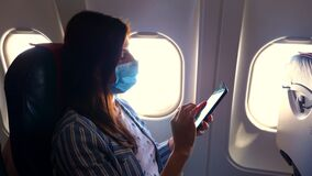 Young woman in a protective mask uses a mobile, smartphone inside airplane, sitting near an illuminator. Resumption of