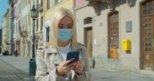 Young woman in protective mask using smartphone in the street of old city. Worried girl searching news about Covid-19