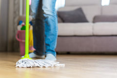 Woman in protective gloves using a wet-mop while cleaning floor. Young woman in protective pink gloves using a wet-mop while cleaning floor in house royalty free stock photography