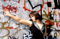 Young woman and protest expressions. Young brunette on front wall of graffiti Royalty Free Stock Image