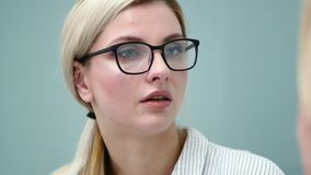 Young woman psychologist in glasses is emotionally talking with her client. stock video