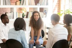 Young woman psychologist sitting in circle among diverse people talking stock image