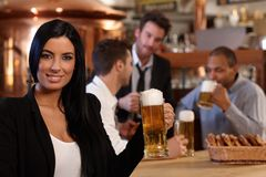 Young woman in pub with mug of beer. Portrait of beautiful young women holding mug of beer in pub, looking at camera, smiling. Friends drinking in background stock image