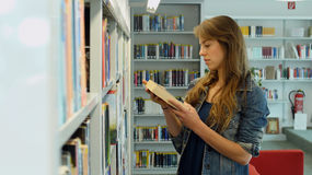 A young woman in a public library. It's her leisure time and she is looking for some good books to read royalty free stock images