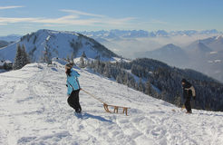Young woman pull sledge to the mountain top Royalty Free Stock Image
