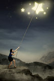 Young woman pulling bright stars Stock Image