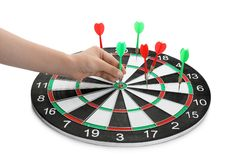 Young woman pulling dart out of board on white background. Closeup royalty free stock photo