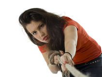Young woman pulling grey rope, tug-of-war Stock Photo