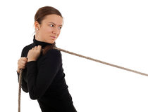 Young woman pulling grey rope, tug-of-war Royalty Free Stock Image