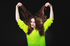 Young woman pulling her long hair. Royalty Free Stock Photography