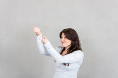 Young woman pulling imaginary rope with her hands Royalty Free Stock Photos