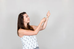 Young woman pulling imaginary rope with her hands. Studio shot of young smiling woman pulling an imaginary rope with both hands Stock Photo