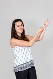 Young woman pulling imaginary rope with her hands. Studio shot of young smiling woman pulling an imaginary rope with both hands Royalty Free Stock Images