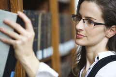 Young woman pulling out book Stock Images