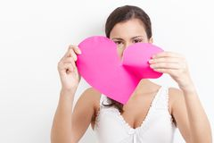 Young woman pulling paper heart to pieces. Young woman pulling pink paper heart to pieces Stock Photos