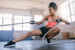 Young woman pulling rope at gym. royalty free stock image