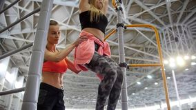 Young woman pulls up on the crossbar in the sports hall. Pumping lower parts of her body with trainer helping her